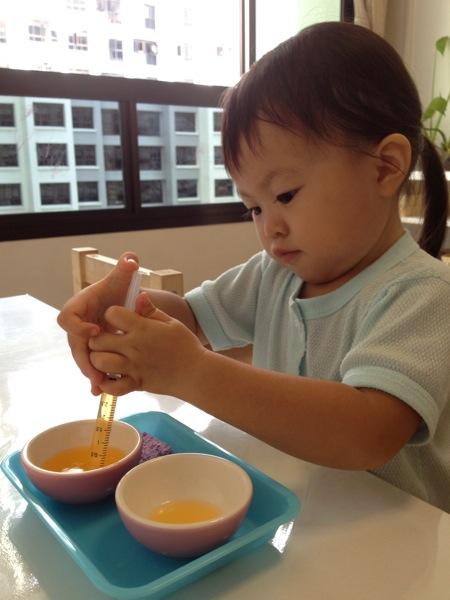 Montessori child at work with syringe